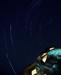 A four-hour time exposure photograph of the night sky showing star trails and with a geodesic home in the foreground.