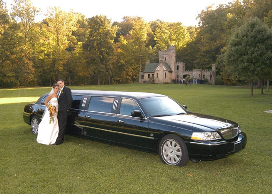 Bride and Groom posing with limousine in front of Squire's Castle