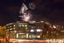 The Gund Arena now called Quicken Loans Arena in Cleveland, Ohio at night with fireworks above and behind.