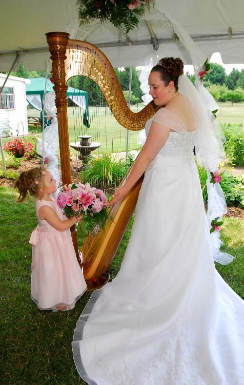 Bride playing harp with flower girl looking on