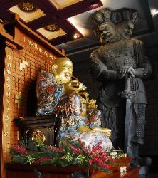 photograph of a golden happy Buddha with a huge statue of a three headed guard watching over at the Chung Tai Chan Monastery in Taiwan