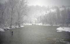 Man fishing in the Rocky River, Ohio during a snowstorm