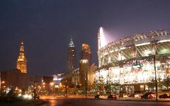 Photo at night of Jacobs Field (now Progressive Field) with downtown Cleveland, Ohio buildings behind.