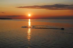 Sunset over a glass smooth Lake Erie with a pleasure boat moving through the sun's reflection