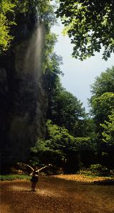 photograph of 60' tall waterfall falling on woman with outstretched arms in Hocking Hills State Park, Ohio