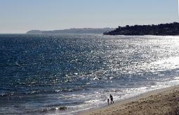 photograph of Malibu Beach and Pacific Ocean with parent and child walking