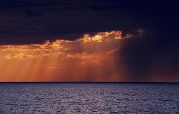 Passing rainstorm over Lake Erie backlit by setting sun