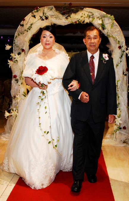Asian bride and father walking down the aisle