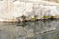 photograph of a wall which is part of an old lock along the Ohio and Erie Canal that is cracked and ver interesting, reflected in the still waters that border it.