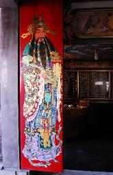 photograph of a red painted door to a temple depicting a Chinese figure