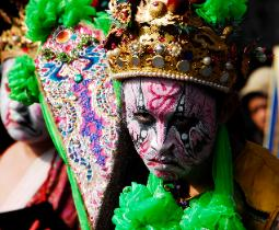 Close-up photograph of a participant in a festival in Taiwan whose face is painted and has an ornate crown of jewels and feathers and fan.