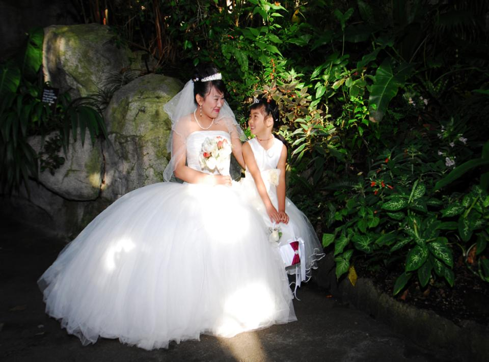 Aaian bride and flower girl in park setting