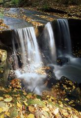 Waterfall in Cleveland, Ohio's metroparks with yellow fall leaves on the ground