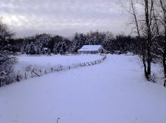 serene winter snow field and pasture with barn in the background